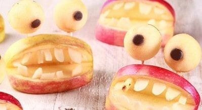 DENTIERE DI MELA  Crea delle simpatiche dentiere di mela semplicemente tagliando una mela in 4 parti e facendo all'esterno un'incisione della larghezza di un dito per creare il foro per la bocca. Successivamente scava con un cucchiaio la polpa di una mela ottenendo così due palline alle quali vanno applicate una goccia di cioccolato ciascuna. Utilizza successivamente degli stuzzicadenti per gli occhi e delle scaglie di mandorla per creare i denti. Sbizzarrisciti con i tuoi amici!